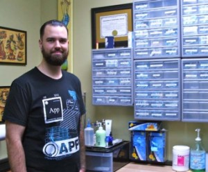 Jeremiah Currier in a private room where he performs body piercings at Highland Square's Good Life Tattoos & Piercings.