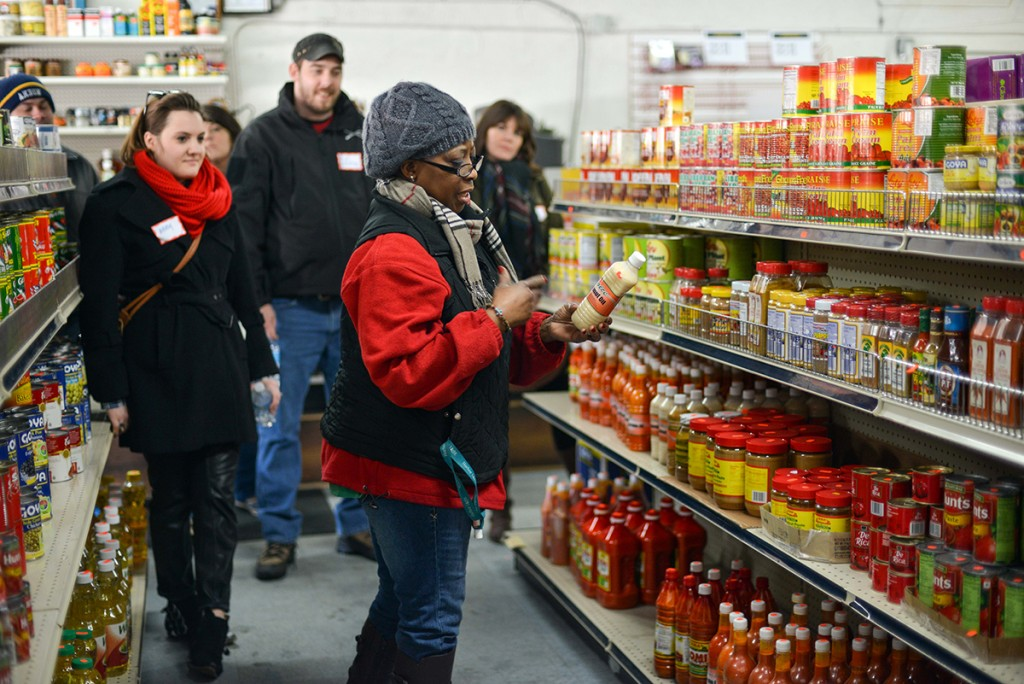 Louise, from Morris' International Market, shares information about African cuisine with the tour group. (Photo: Shane Wynn)