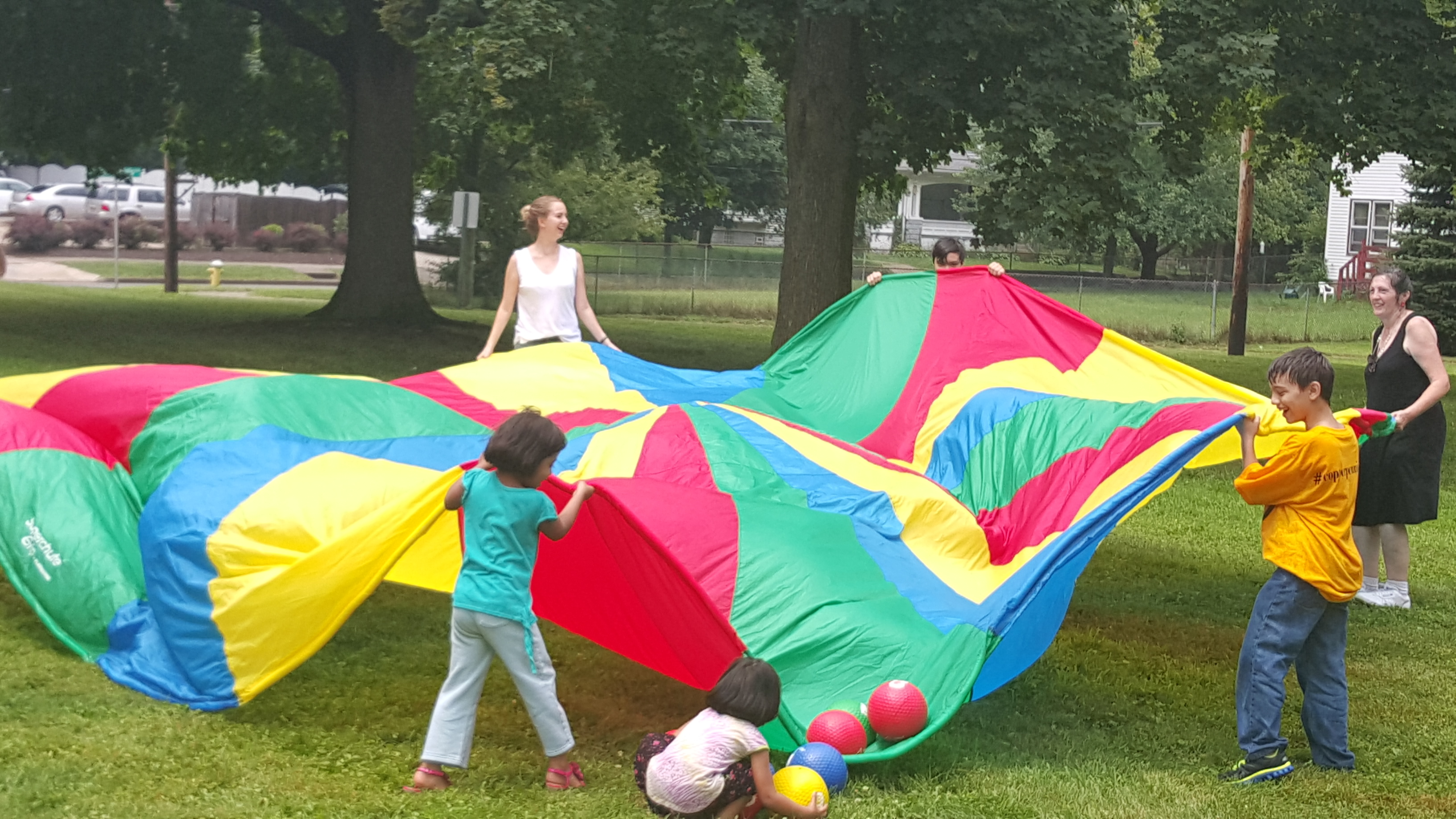 Maria Mancinelli and Sylvia Gage teach children how to bounce balls off the parachute