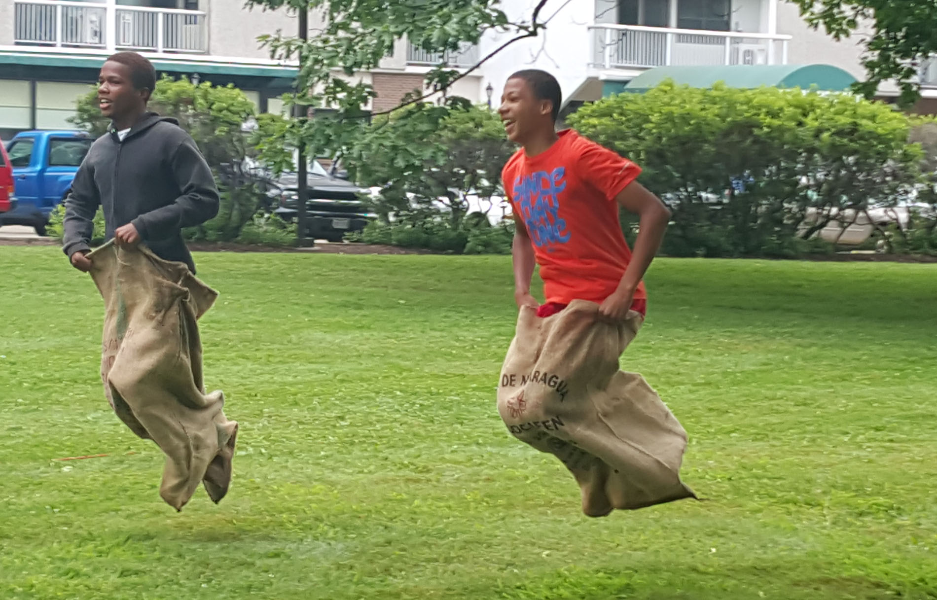 Dante Berry and Mujahid Moore enjoy the potato sack races at the North Hill Open Fresh Outdoor Market's inaugural Kids Day. (Photo Yoly Glez M. Heisler)