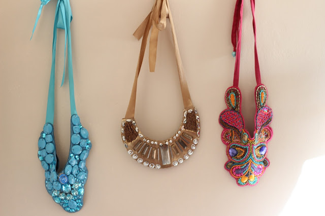 Bulky statement necklaces hung on wall with thumb tacks. You could even use fancy drawer hardware to hang accessories.