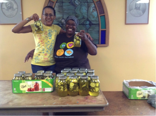 Grace Hudson and Sandra Saulsberry display pickles produced by the community.