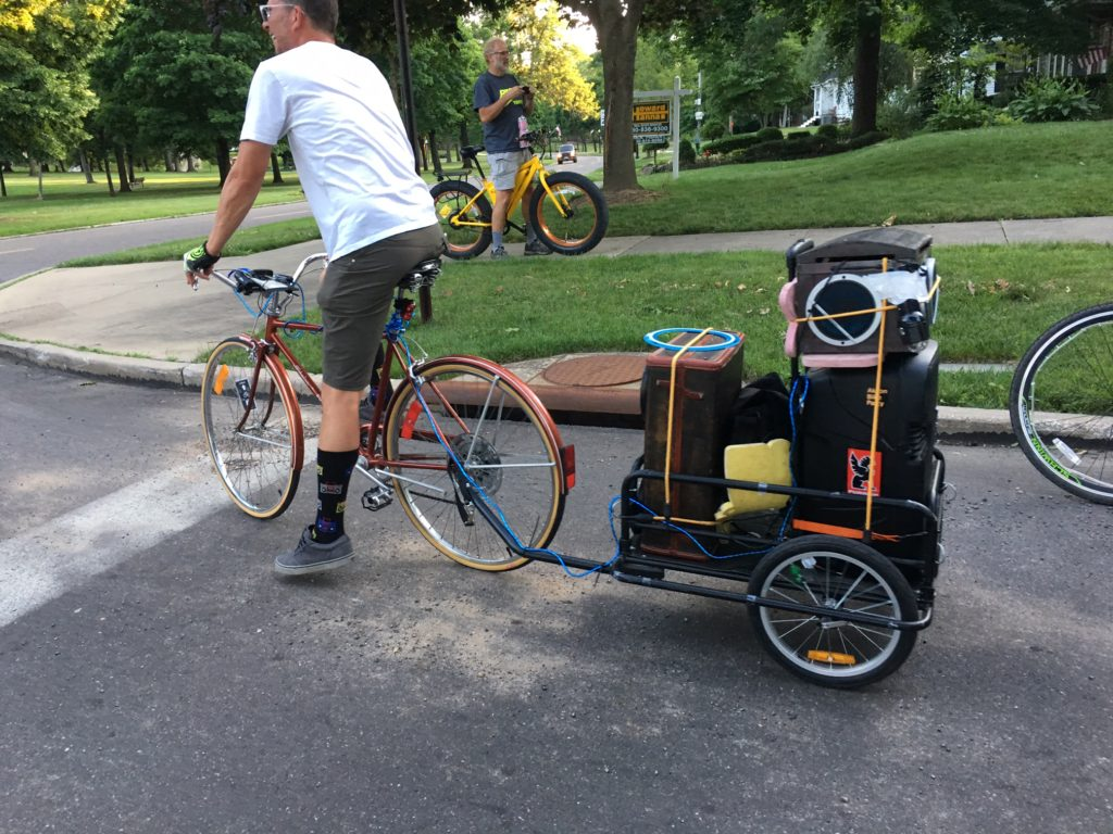 Akron Bike Party Founder Dave Massary pulls a trailer with a speaker playing music for fellow bicyclists during the group's June ride. (Photo: Chris Miller)
